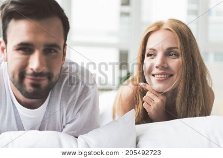 Portrait of pretty young woman looking at her husband with affection. They are lying on beddings and laughing