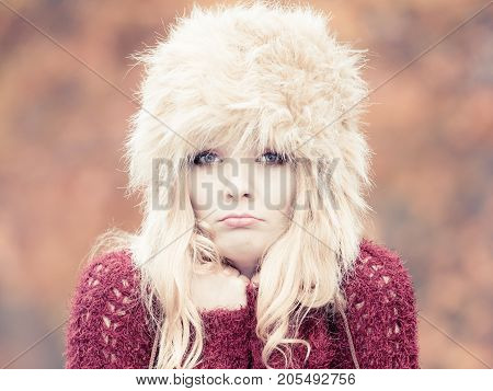 Portrait of pretty fashionable woman in fall forest park feeling cold. Gorgeous young girl in fur winter hat and sweater shivering. Autumn fashion.