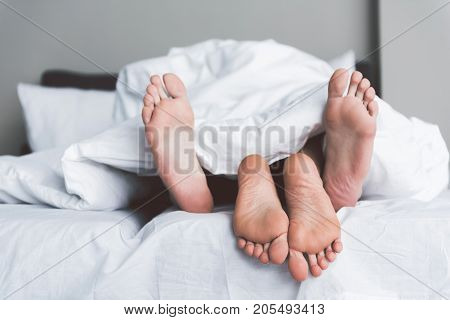 Close up of male and female bare feet. Young couple is luxuriating in bed covered by white blanket. Focus on their legs