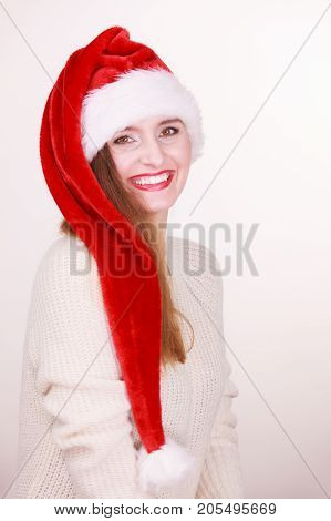 Christmas time. Young smiling lady wearing santa claus hat. Celebration holiday concept.