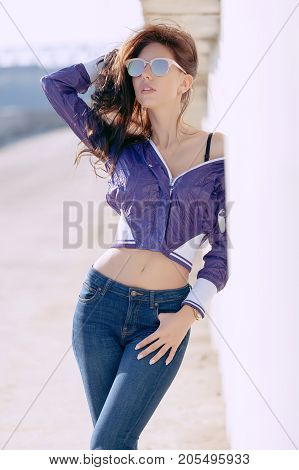 Fashionable Young Woman In Sunglasses, Lilac Short Windbreaker And Jeans. It Stands On A Concrete St