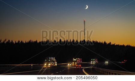 High way with heavy vehicles in driving the night, a tree line silhoutte i the background with a cell tower and a moon in the waxing crescent. Colorful blue yellow sky.