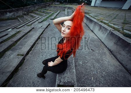 Style redhead girl sitting on outdoors. Woman with vibrant colorful hairstyle holding her hair and looking to camera. Wide angle portrait.