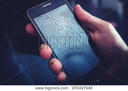 Broken Smartphone Display. Crashed Cellphone in Hand.