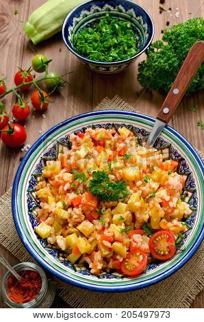 Rice pilaf with vegetables. Vegetarian dish with rice carrots onions bell peppers zucchini and lots of spices