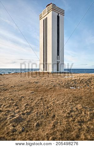 Beautiful lighthouse on the brown grass on the seashore of Iceland on the background of the blue sky with clouds. Sun shines onto it. Vertical.