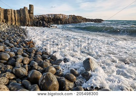 Landscape with rocky seashore and stormy sea and blue sky with clouds. Sun is shining. Waves are breaking on the boulders. Panoramic horizontal photo.