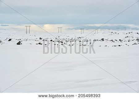 Power line on the snow field with stones on the cloudy sky background in Iceland. Horizontal.