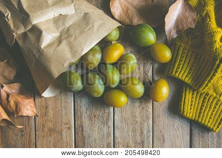 Yellow Green Plums in Brown Craft Paper Bag Scattered on Plank Wood Table Dry Autumn Leaves Knitted Sweater Fall Cozy Atmosphere Template Copy Space