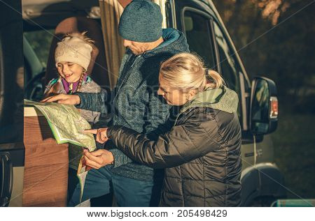 Family Camper Trip Planning. Young Caucasian Family Taking Look on the Map in the RV Motorhome Side Doors. poster