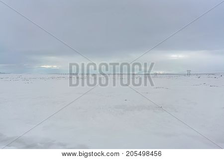 Panoramic view at the power line on the snow field on the cloudy sky background in Iceland. Horizontal.