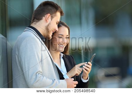 Two Executives Using A Mobile Phone On The Street