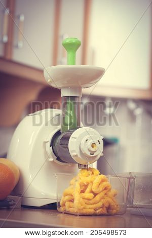 Making Orange Juice In Juicer Machine In Kitchen