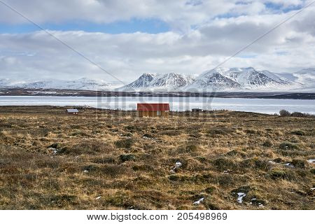 Country houses on the brown field on the background of the bay, snow mountains and cloudy sky in Iceland. Panoramic horizontal photo.