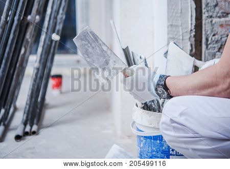 Home Remodeling Concept. Caucasian Worker with Construction Tools and Scaffolding in the Background. Apartment Finishing.