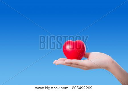 Heart in the hand on sky background with hope and charity concept.