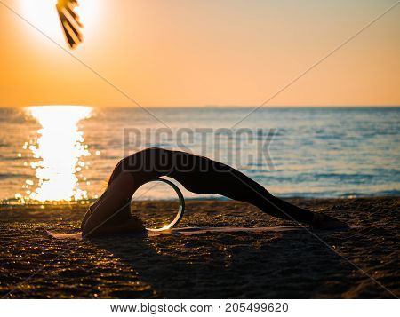 Silhouette of beautiful young woman practicing morning yoga on sand sea beach with yoga wheel.
