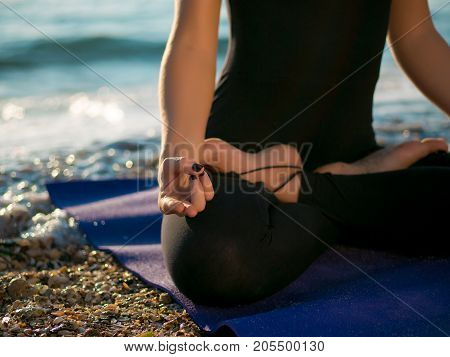 Beautiful young woman practicing morning yoga in lutus pose on sand sea beach. Meditation concept.