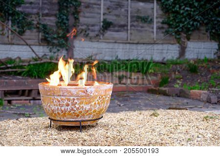 A clay outdoor fire pit in back garden in cold autumn evening