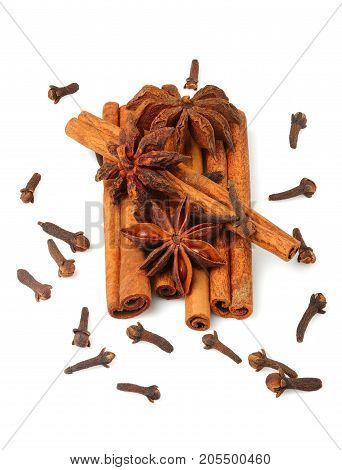 Cinnamon sticks with star anise and cloves isolated on white background.