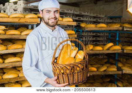 Bakery. Bread. Baker. A Young Handsome Guy Worker At A Bakery On A Background Of Shelving With Bread