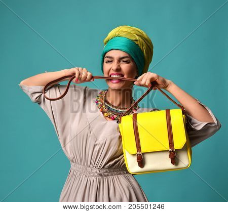 Woman yelling screaming and eating belt of hand hold stylish fashion yellow leather bag handbag isolated on blue mint background