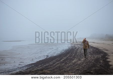 Lonely sad man walking on a foggy beach. Concept of troubles, headache
