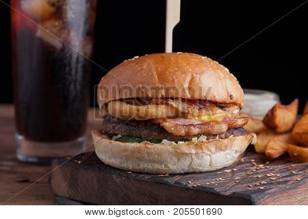 A Tasty Burger With Snacks In The Form Of Potatoes With White Garlic Sauce And A Glass Of Cold Cola.