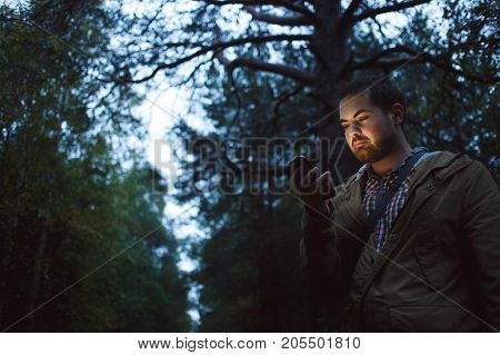 Man has got lost in the wood looks in phone in the evening. Concept of navigation, loneliness, communication. High iso picture.