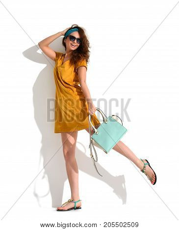 Beautiful woman walking running in yellow brown fashion body dress cloth with blue mint hand bag clutch on a white background