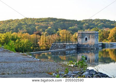 brick and stone castle structure on the water with beautiful foliage in the background and reflecting on the water