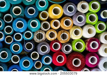 Background of multicolored thread spools from top view