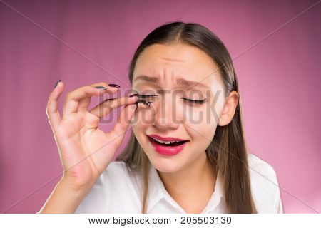 A young woman removes  pastes artificial eyelashes. Eyelash extension, frightened face