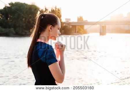 A woman is boxing at sunset by the river