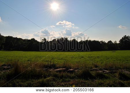 bright yellow sun over the clouds on a blue sky sunny summer afternoon lighting up an open field