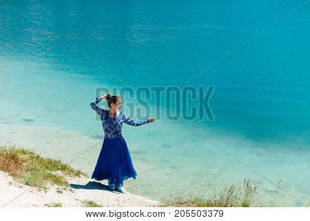 Copy space of silhouette woman rising hands with blue sky and white cloud on beach background. Vintage tone filter effect color style.