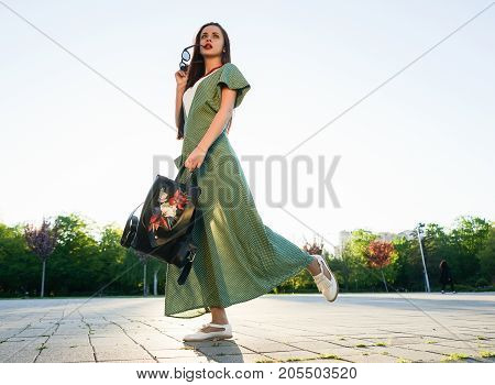 Fashion street style woman with bag in hand,sunset