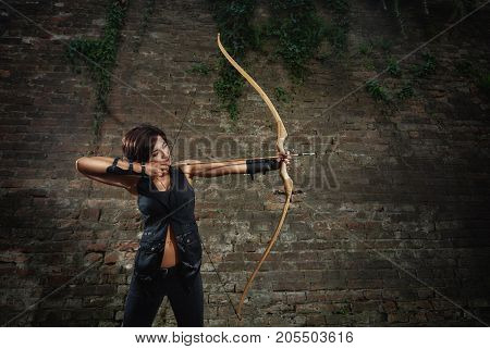 Back view of pretty athletic brunette girl wearing in black leather suite, shooting from big bow. Female with short hair, warrior,  holding arrow and tacking focus, looking at side. Concept of sport.