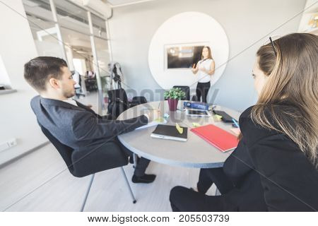 Office workers sit at a table at a meeting
