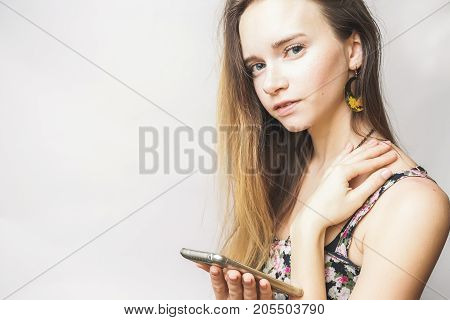 Serious summer happy young woman with smartphone smiling