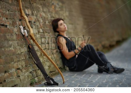 View from distance of young brunette woman in black sitting on road, leaning on brick wall, near bow and arrow. Girl resting after shooting from old weapon. Concept of activity and hobby.