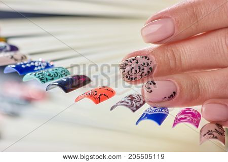 Female fingers with beautiful beige varnish. Young caucasian woman hand with beige patterned manicure and palettes with nail polishes, variety of nail care.