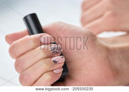 Polish container in female hand. Young womans hand with beautiful manicure holding bottle with nail polish. Feminine treatment and care.