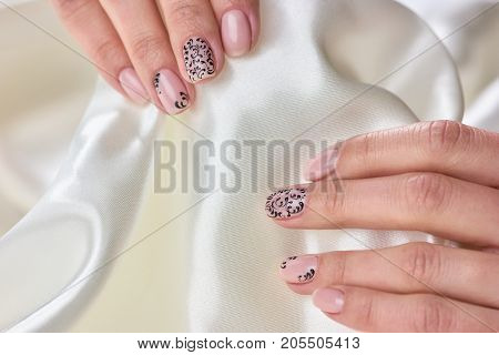 Female manicured hands on white silk. Young woman hands with gentle manicure holding pure white silk fabric. Woman delicacy and care.