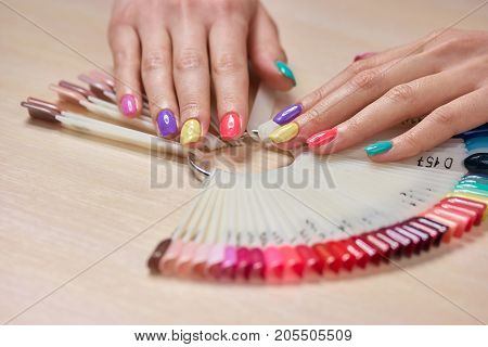 Multicolored summer manicure on female hands. Beautiful pastel manicure on young womans hands, palettes with nail polishes. Salon beauty and spa.