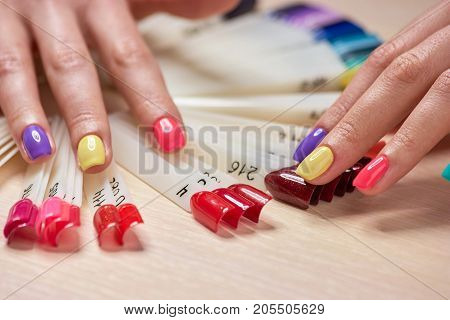 Girls fingers with multicolored nails. Female hands with fashion summer manicure and nails samples. Stylish summer manicure.