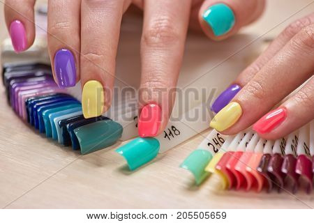 Manicured fingers touching nails samples. Female fingers with bright summer manicure and nails samples. Variety of nails colors in beauty art salon.
