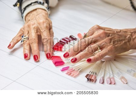 Old woman manicured hands with rings. Senior womans hands with red nail polish wearing rings. Conept of wealth and aristocratism.