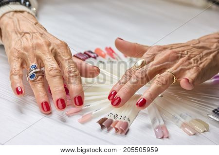 Senior woman manicured hands. Old woman nails covered with perfect red polish, nails samples collection.