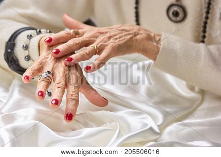 Senior manicured hands with jewelry. Old aristocratic woman hands with beautiful red manicure wearing luxury rings, white silk. Female treatment and wealth.